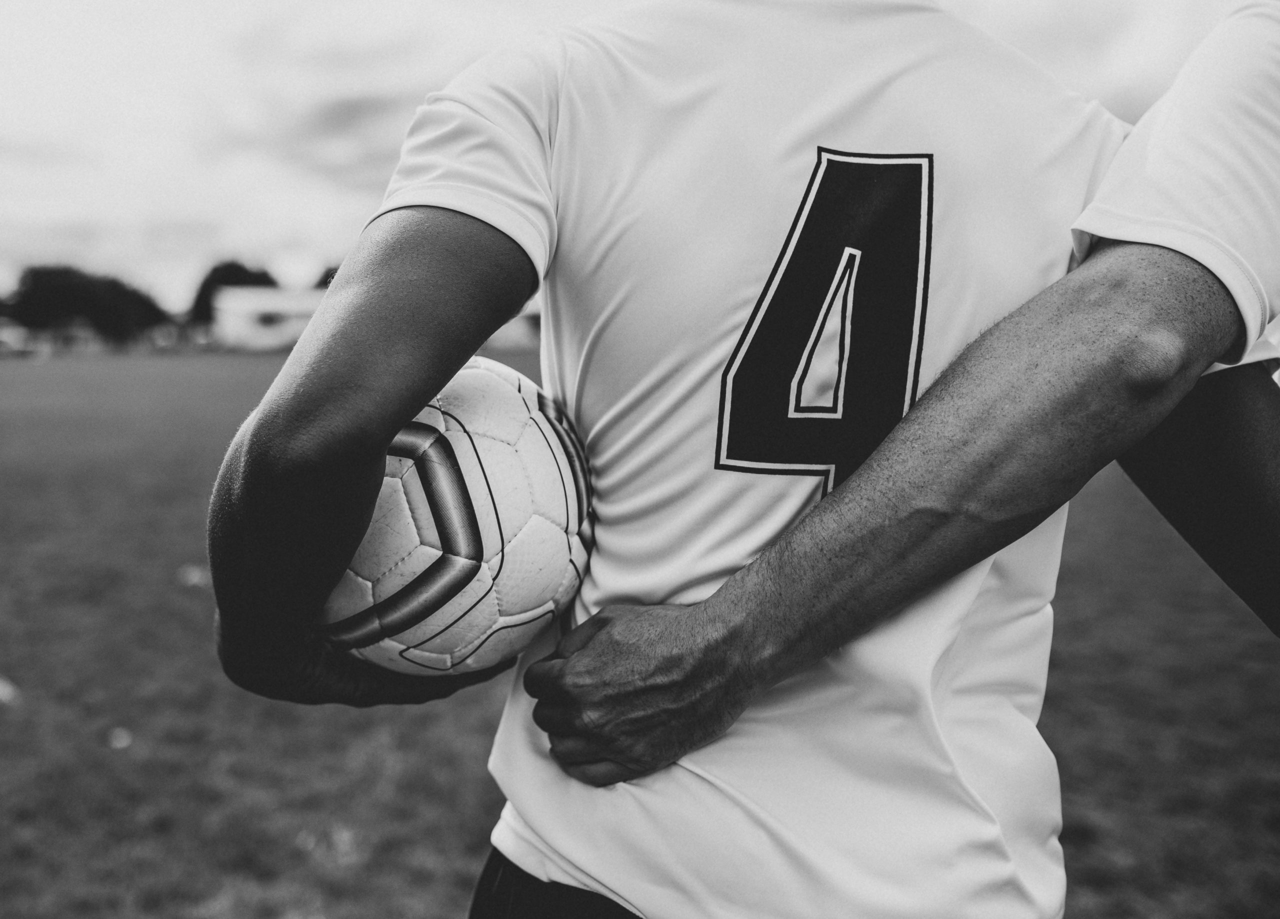Black and white photo of athletes walking arm in arm with a soccer ball.