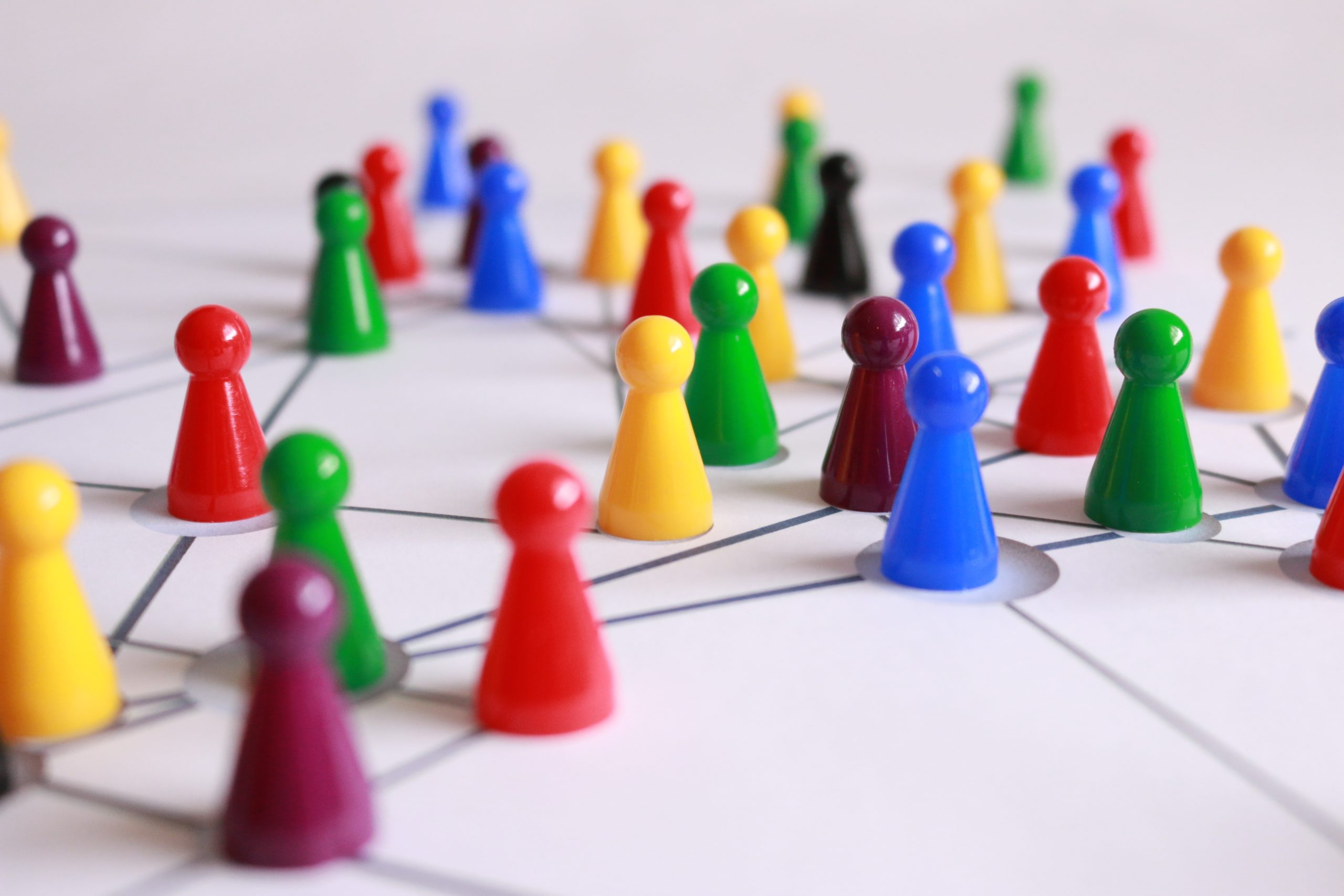 Game pawns of many colors laid out on a white surface.